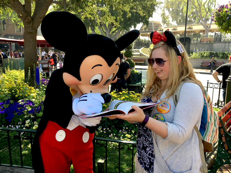 Mickey signs an autograph book